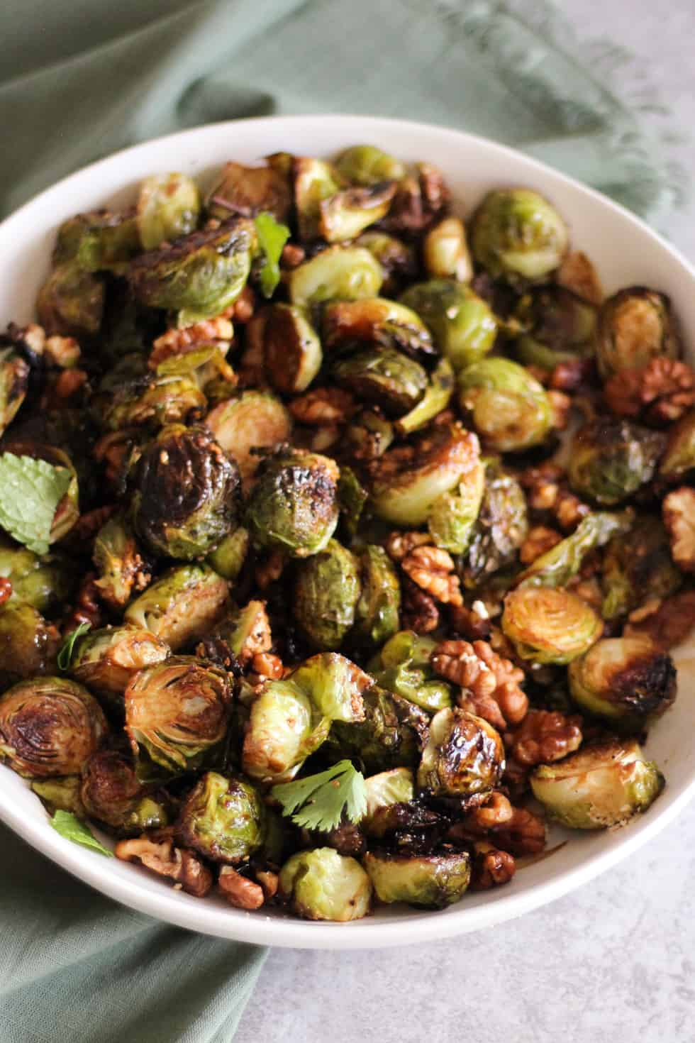 Crispy roasted Brussels sprouts in white dish with green napkin.