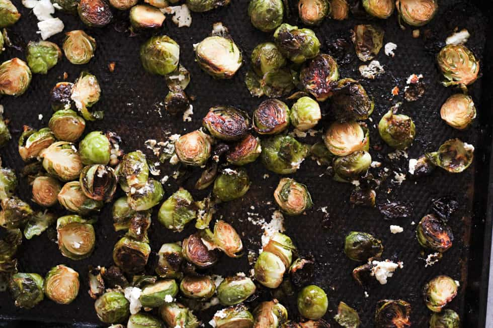 Crispy roasted Brussels sprouts and goat cheese on baking sheet.
