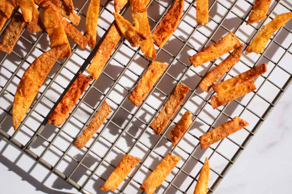 Corn tortilla strips on wire cooling rack.