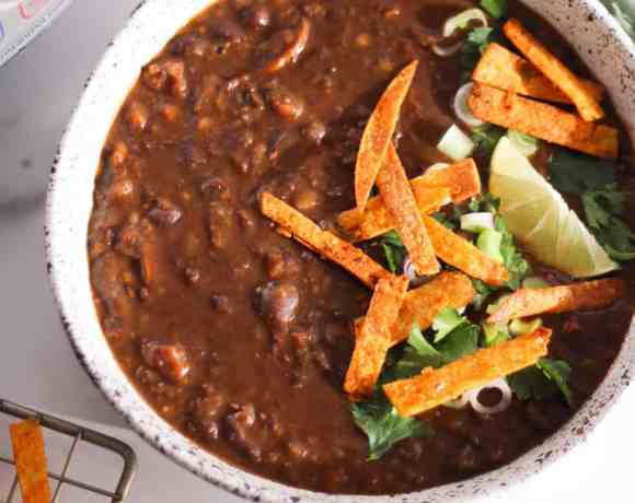 Black bean soup in white bowl with Instant Pot.