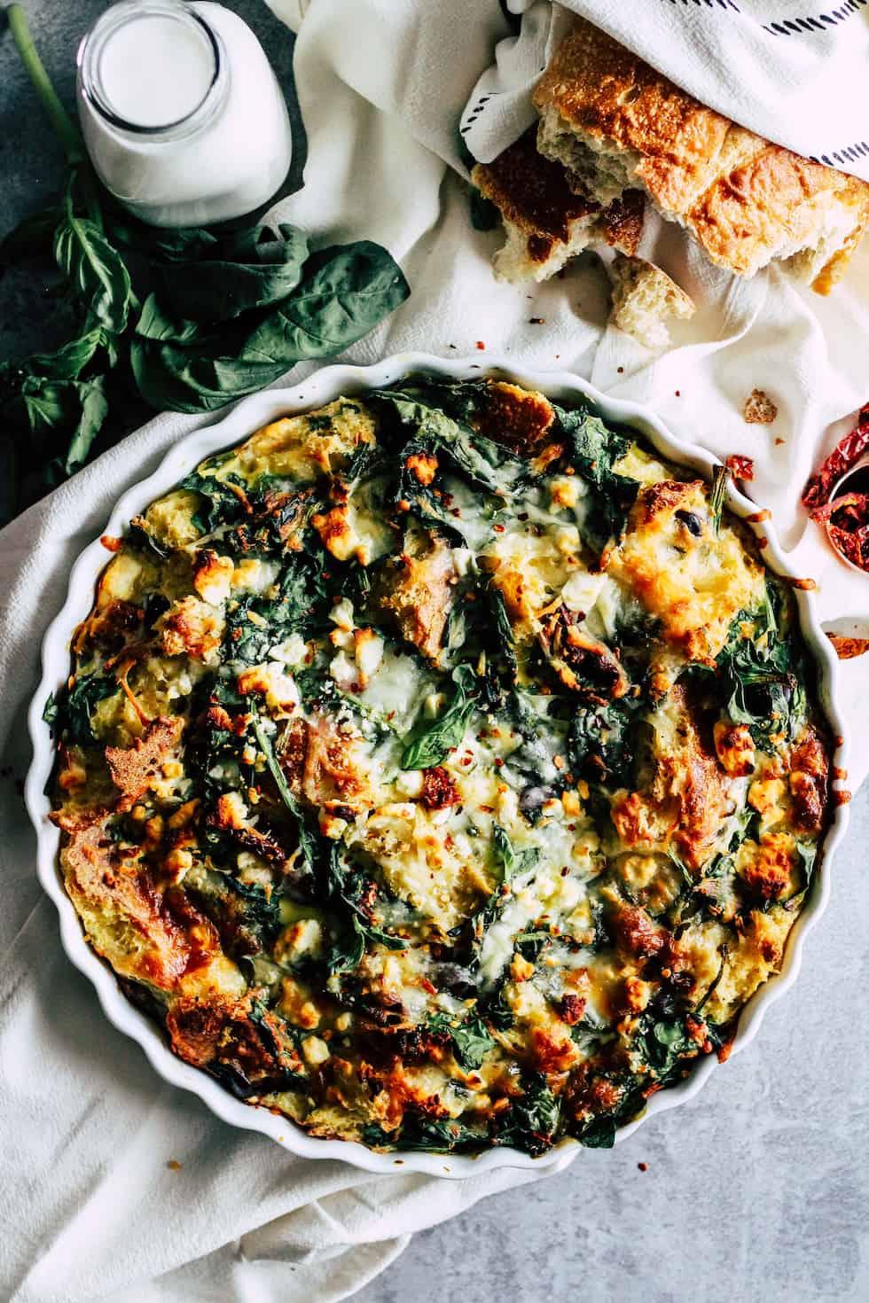 Vegetarian Strata in white pie dish wtih bread and fresh herbs.