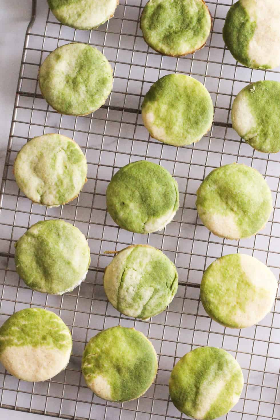 Marbled green and white cookies on wire rack.