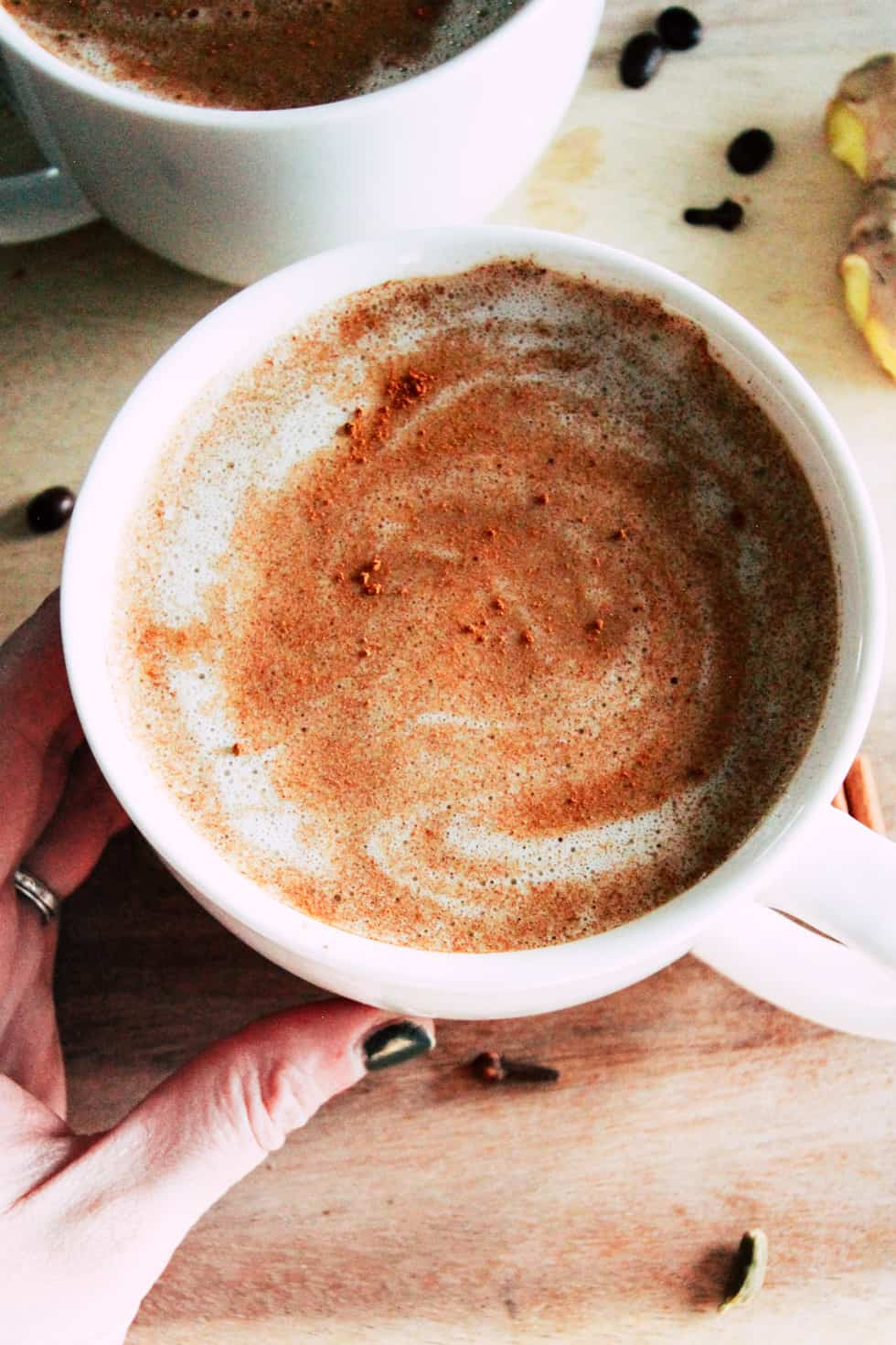 Hand holding a white mug with cinnamon latte.