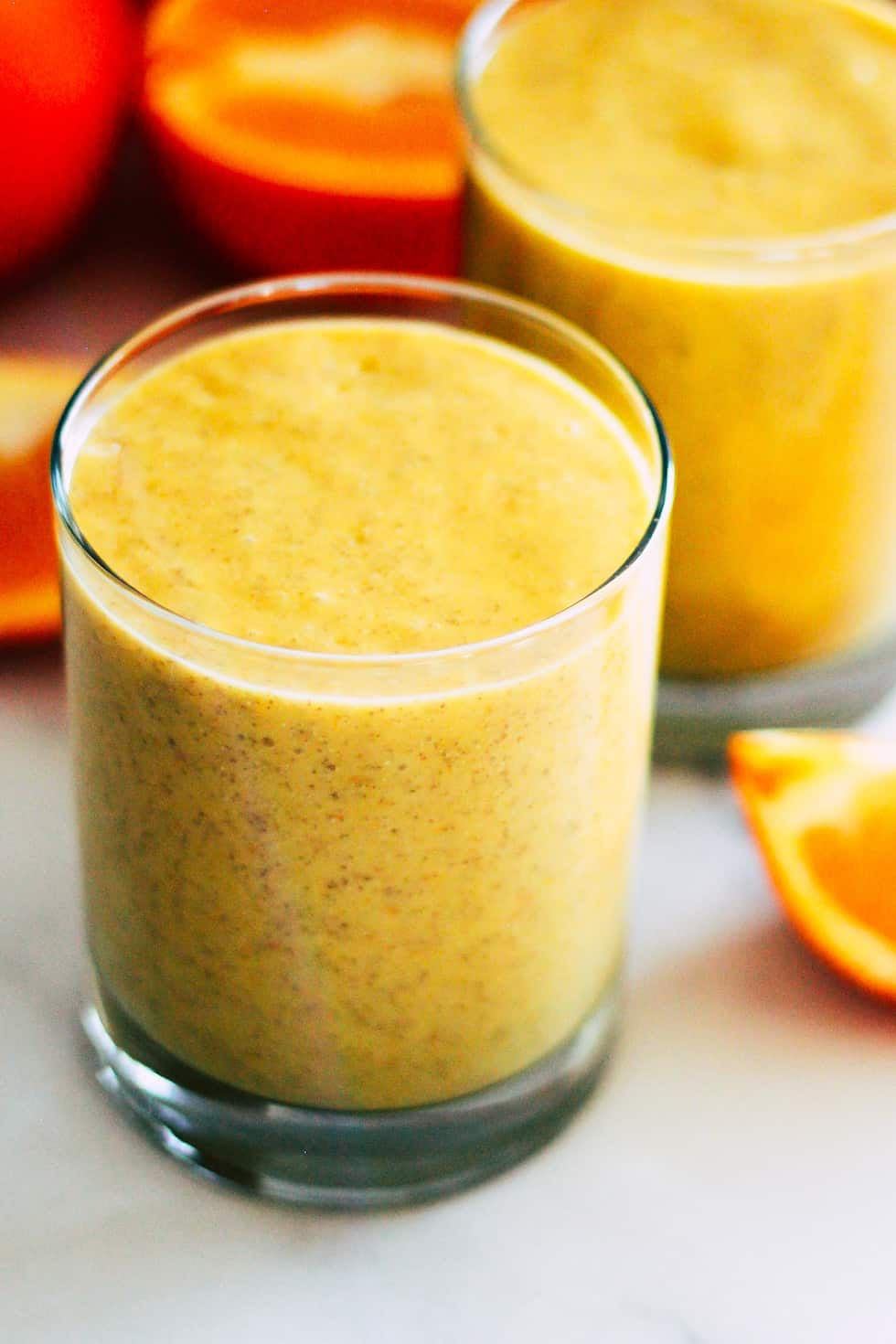 Yellow Mango Orange Smoothie in a glass surrounded by oranges.
