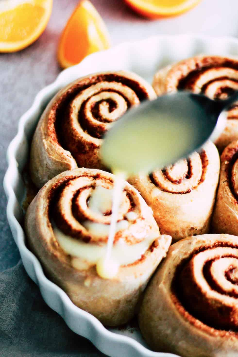 Spoon glazing icing over sweet rolls in a round, white baking dish.
