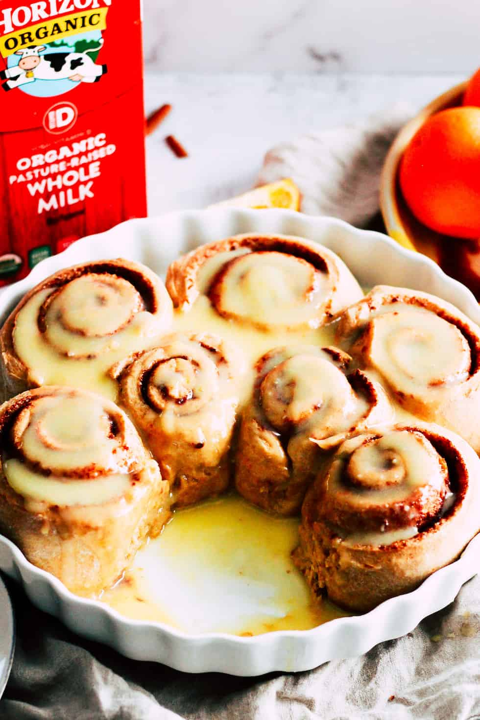 Orange Cinnamon Rolls in a white baking dish with a carton of Horizon Organic milk behind it.