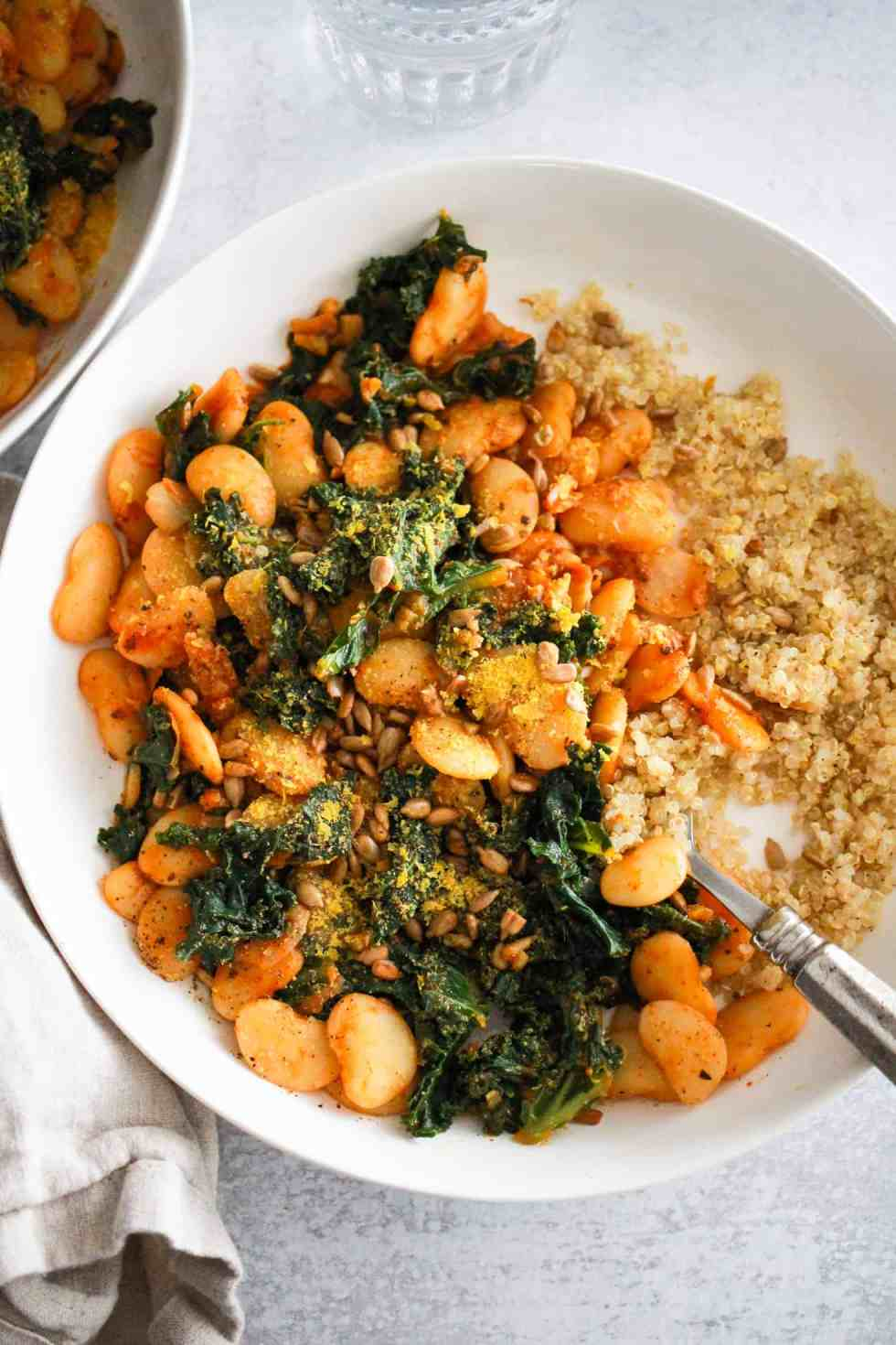 Butter Beans and Greens in a white bowl with cooked quinoa.