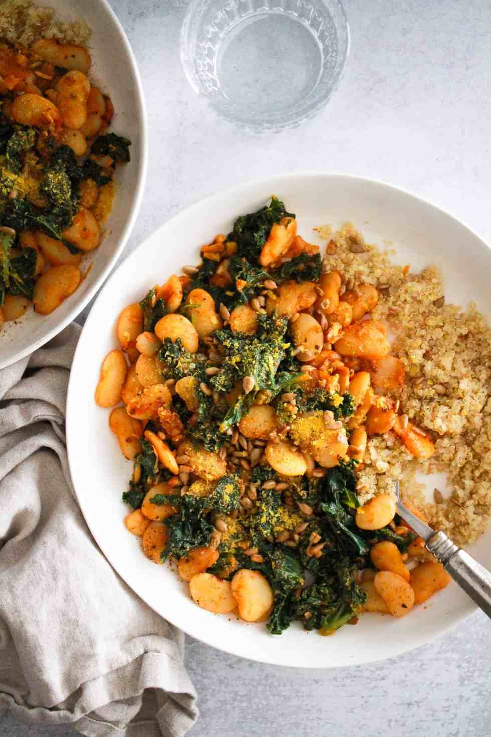 Image of butter beans recipe in white bowls with a water glass and linen napkin.