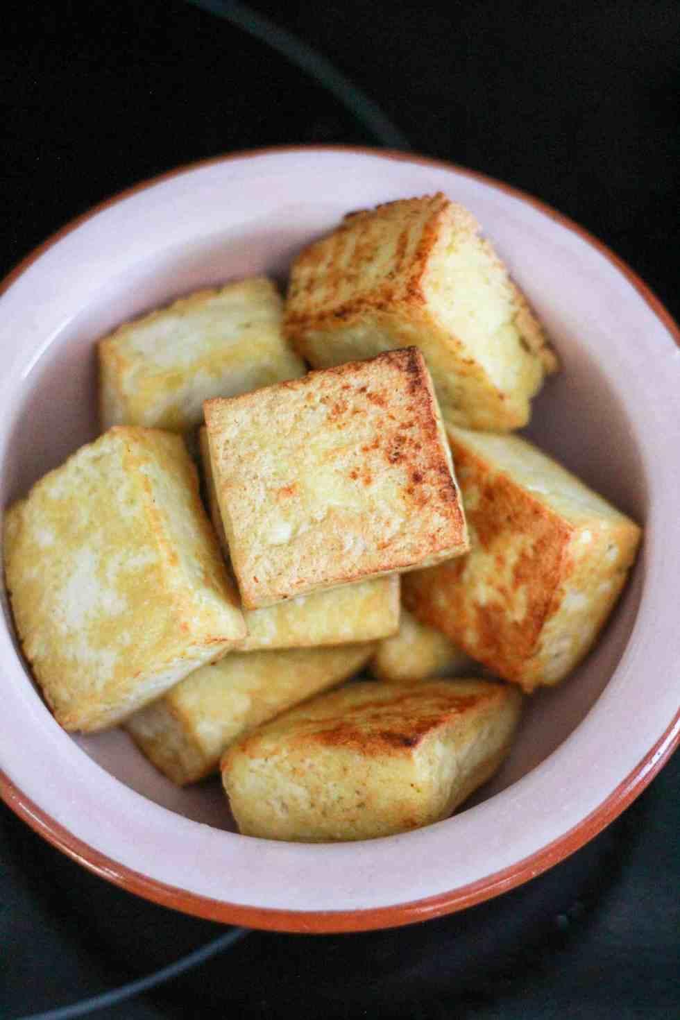 Pan-fried tofu in a pink bowl.