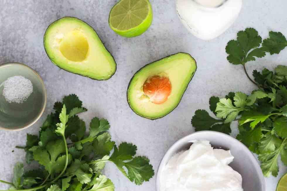 Flat-lay image of avocado crema ingredients: avocado, cilantro, yogurt, milk, lime, and salt.