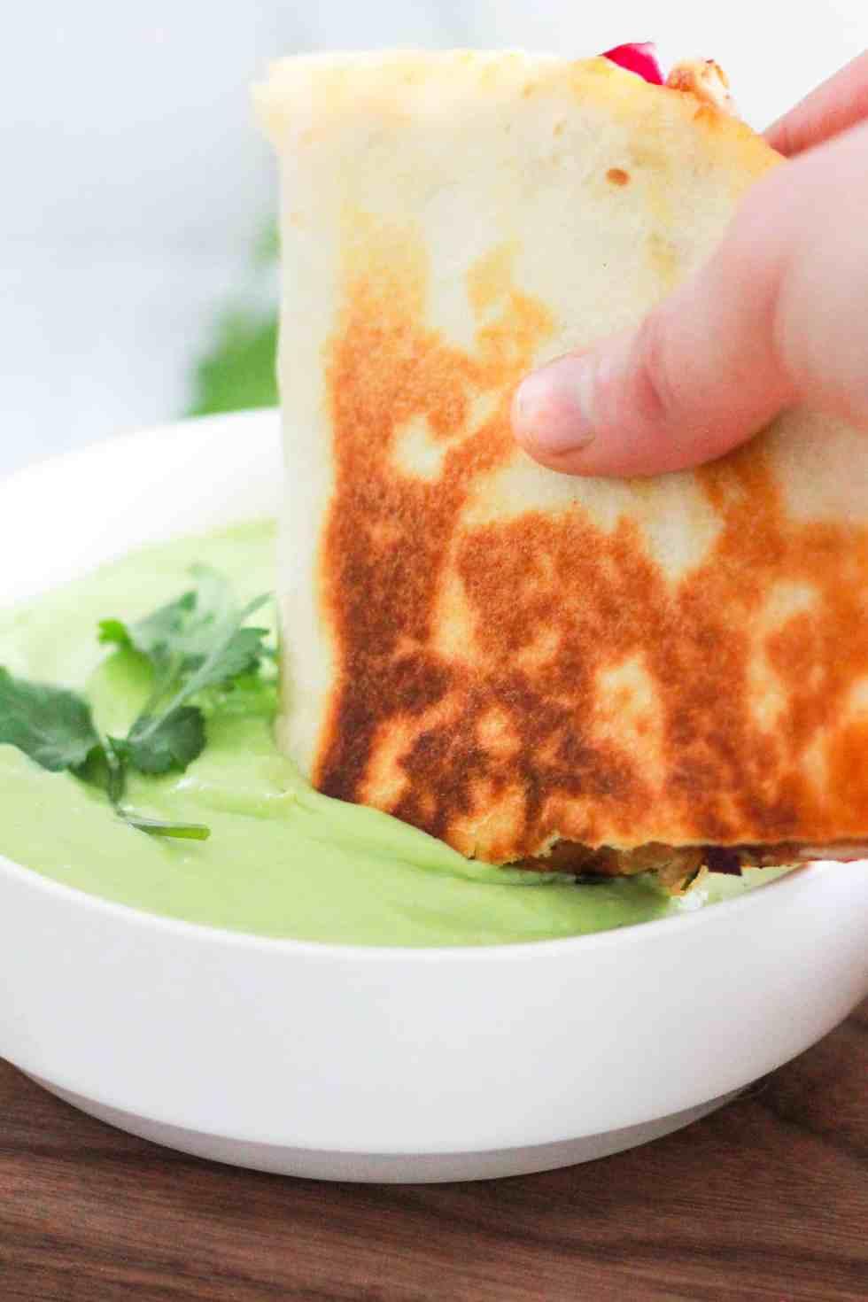 Dipping a vegetarian quesadilla into green avocado crema sauce.