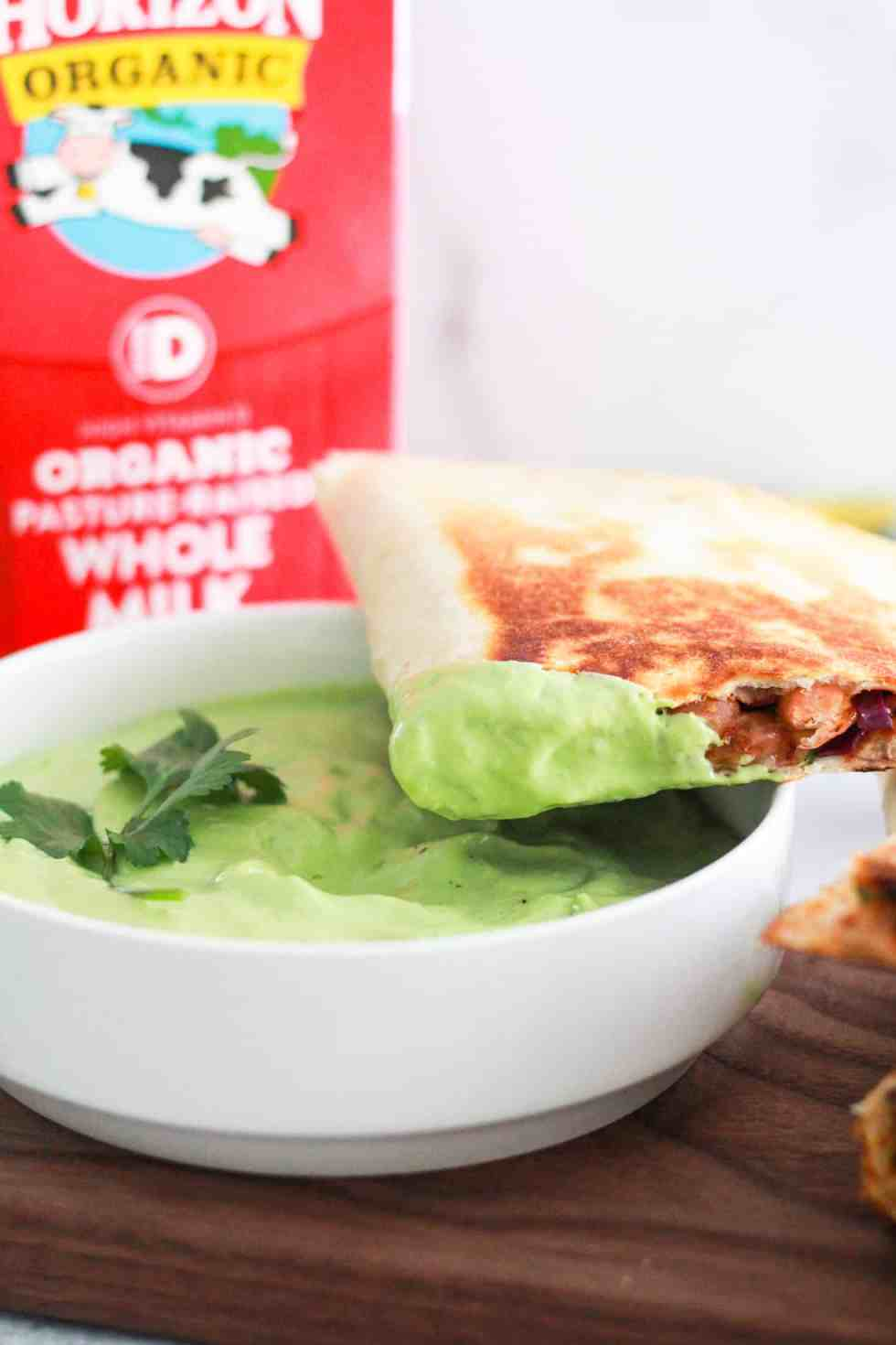 Vegetarian quesadilla dipped in green sauce with carton of Horizon Organic milk behind it.