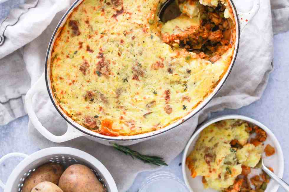 Horizontal image of white dutch oven with tempeh shepherd's pie and gold potatoes in white basket.