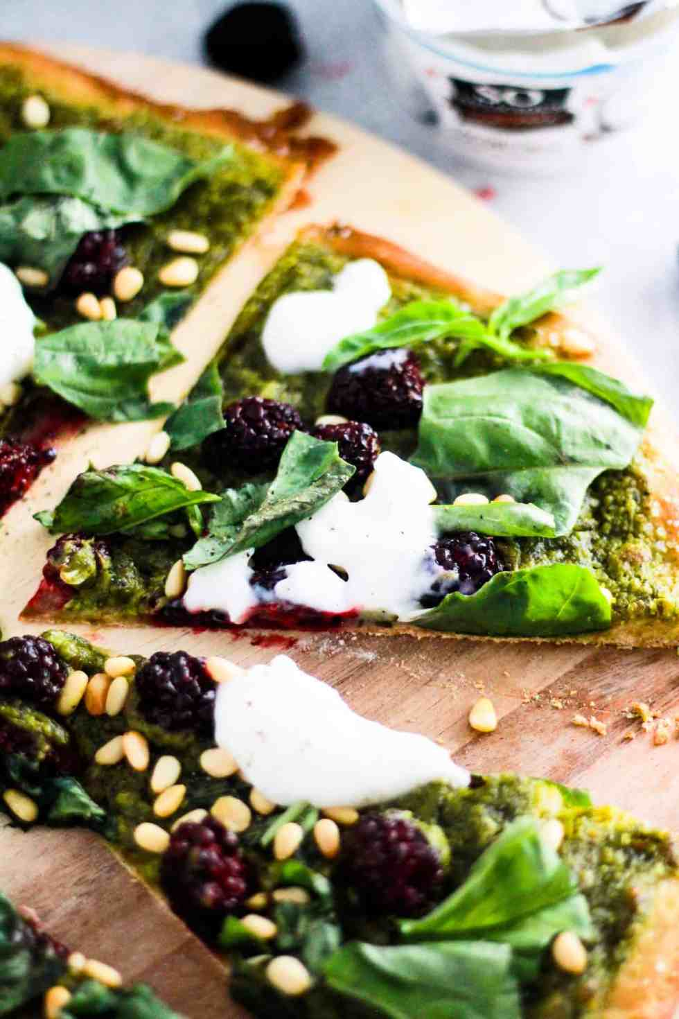 Vegan pesto pizza slices on wood board with So Delicious Coconut Milk Yogurt behind it.