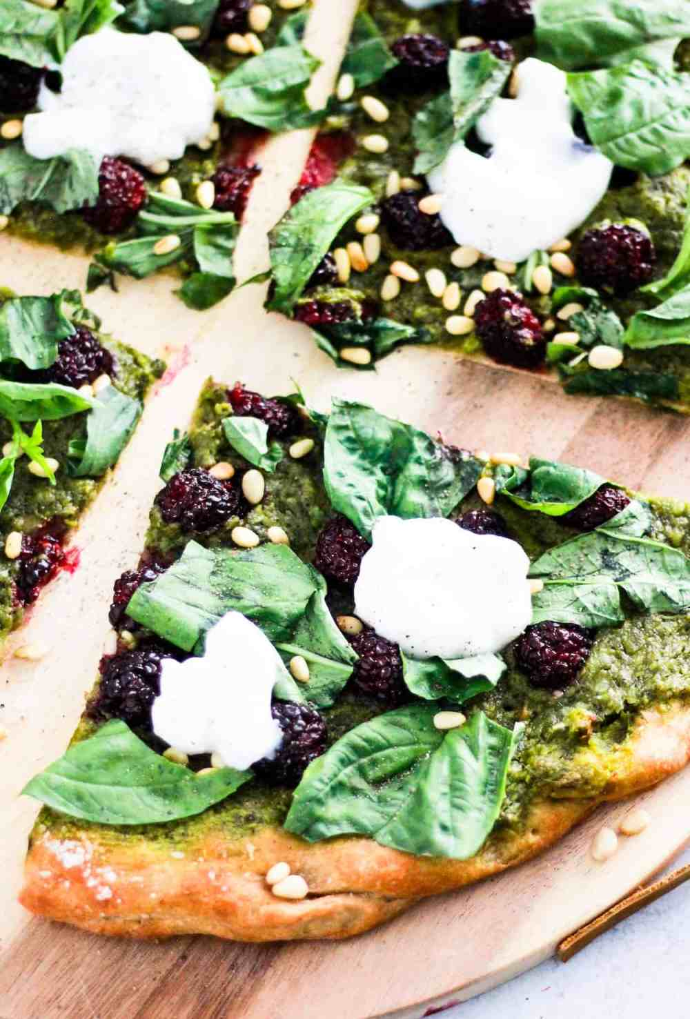 Sliced green Vegan Pesto Pizza with blackberries on wood board.
