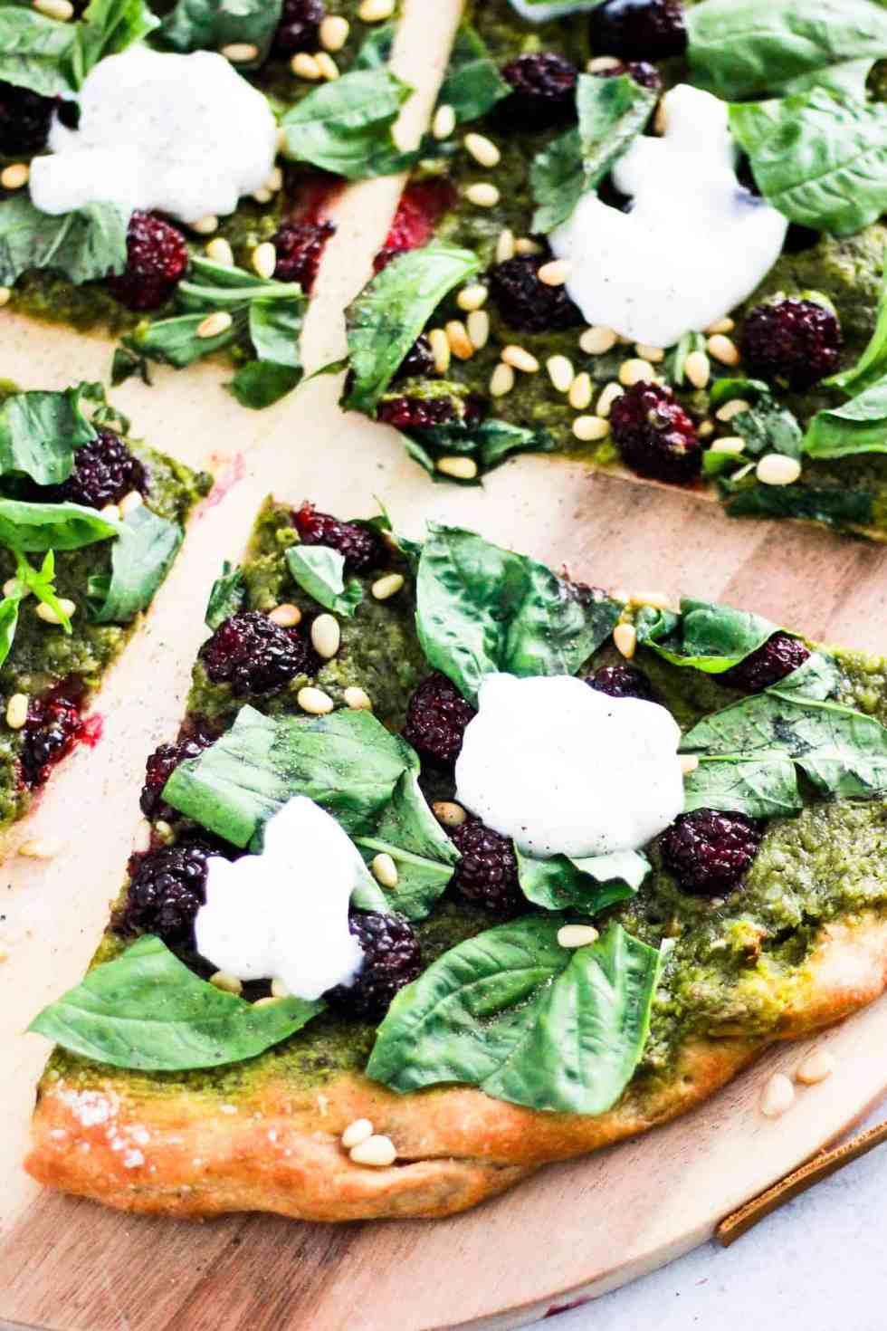 Sliced green Vegan Pesto Pizza with blackberries on wood board.