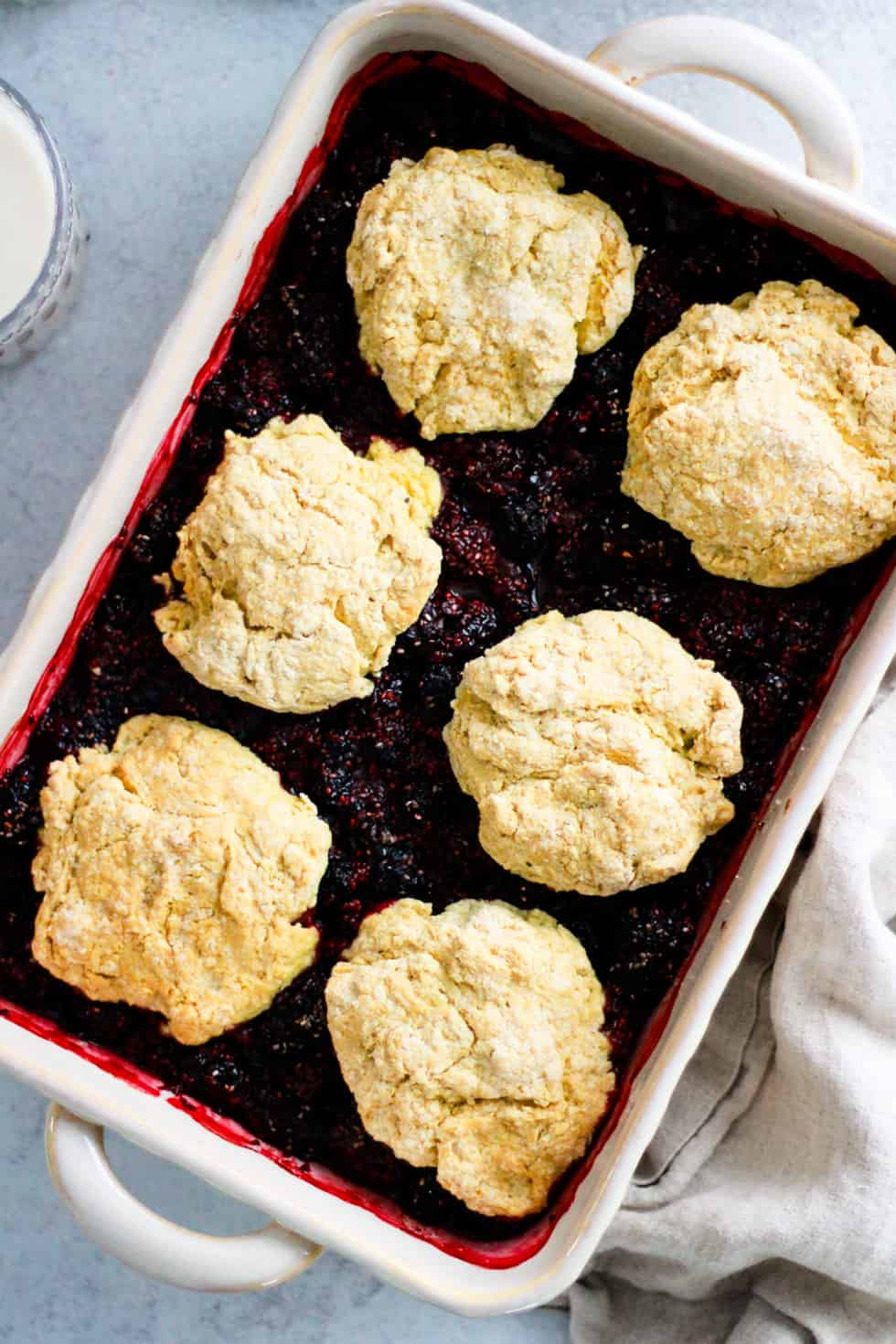 Berries covered with whole wheat biscuit topping in a white baking dish.