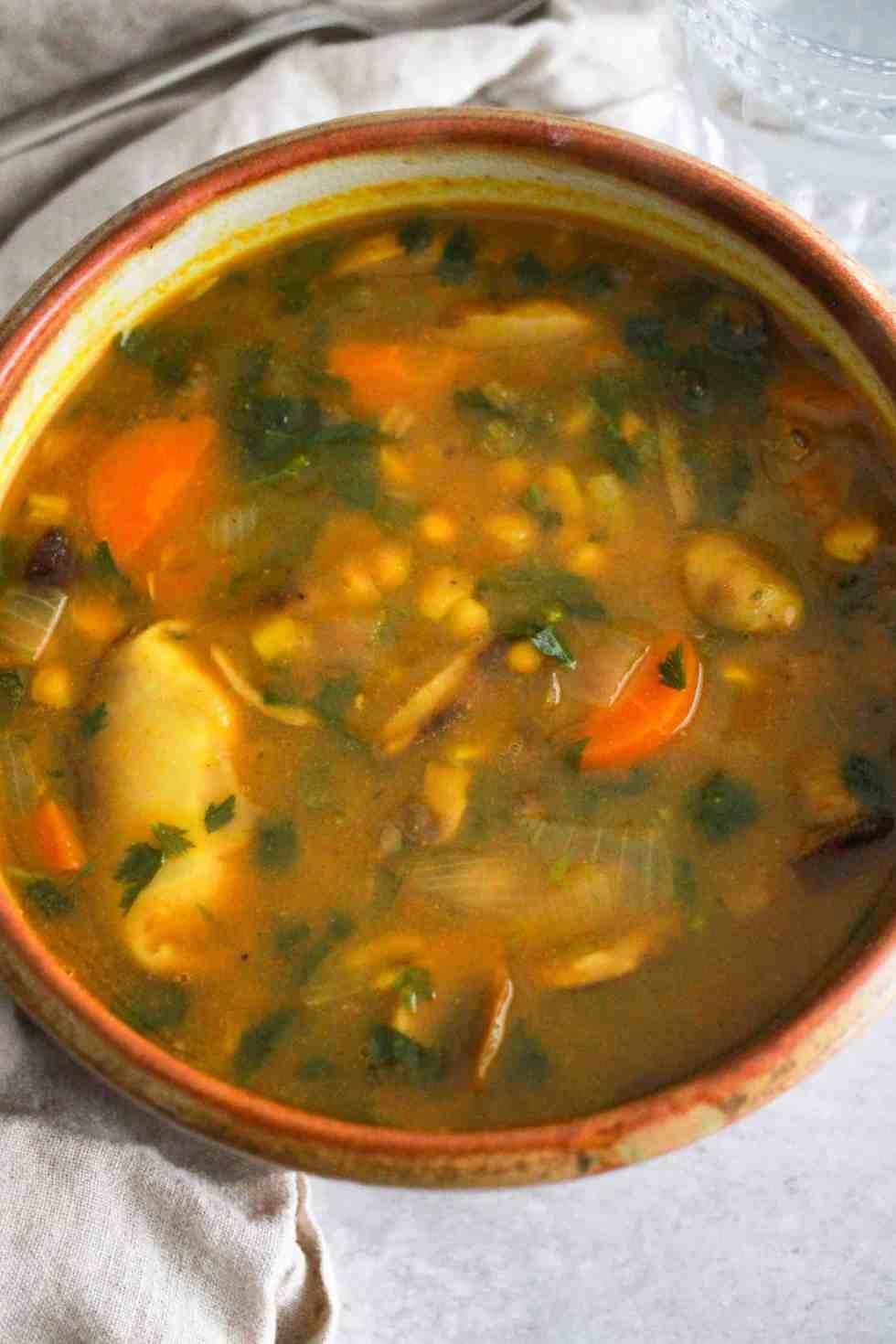 Yellow split pea soup in brown ceramic bowl.