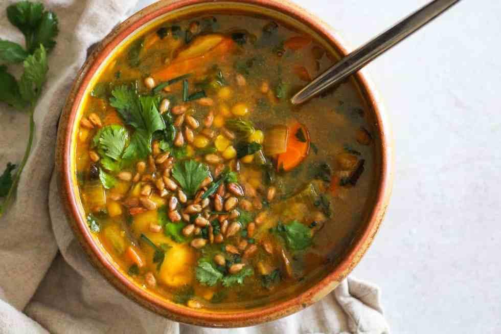 Horizontal image of yellow pea soup in brown ceramic bowl.