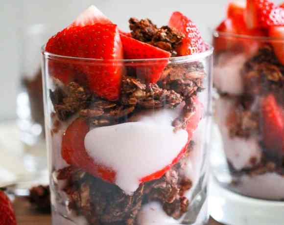 Vegan strawberry yogurt parfait in glass with chocolate granola.