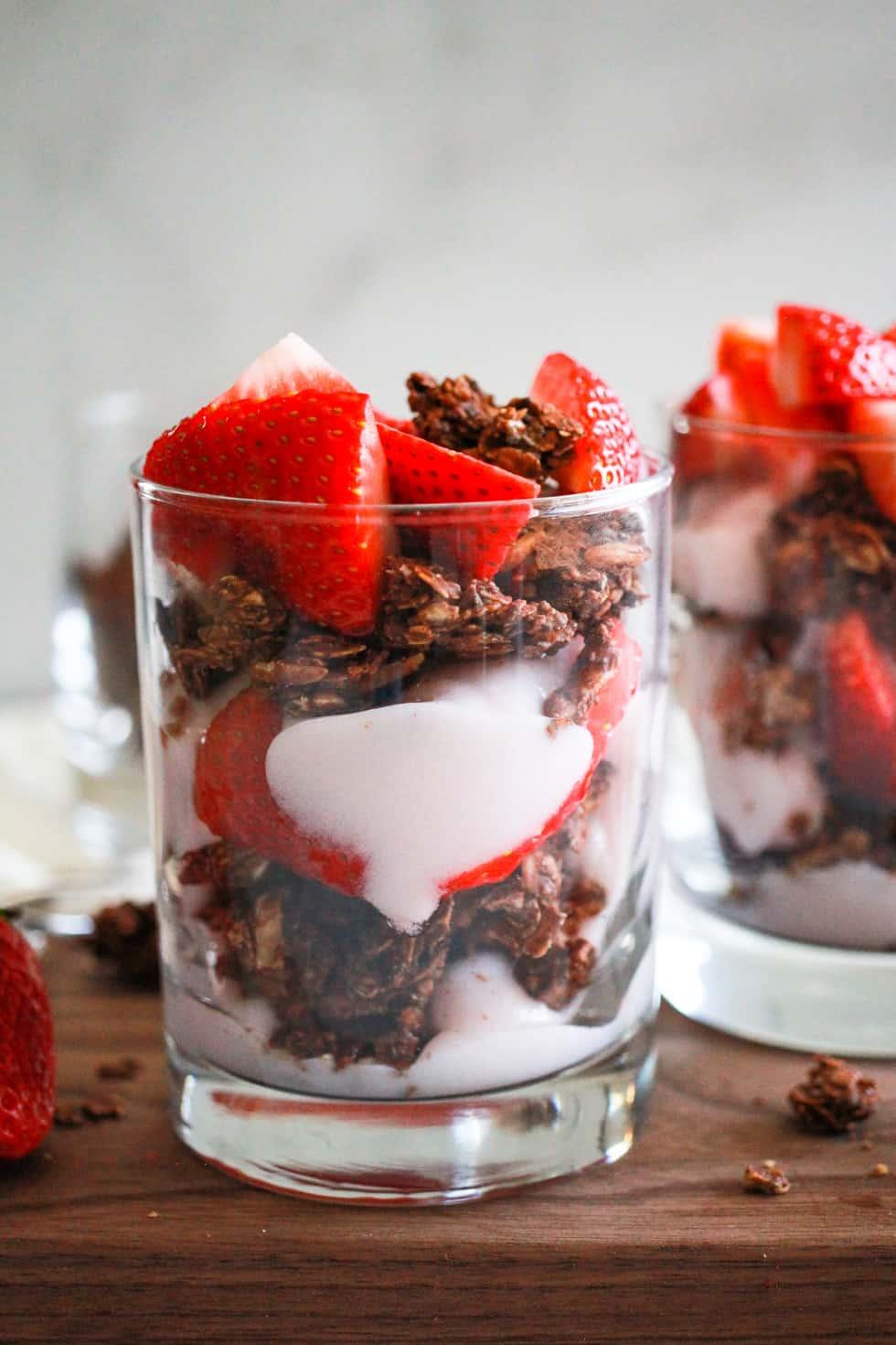 Vegan strawberry yogurt parfait in glass with chocolate granola.