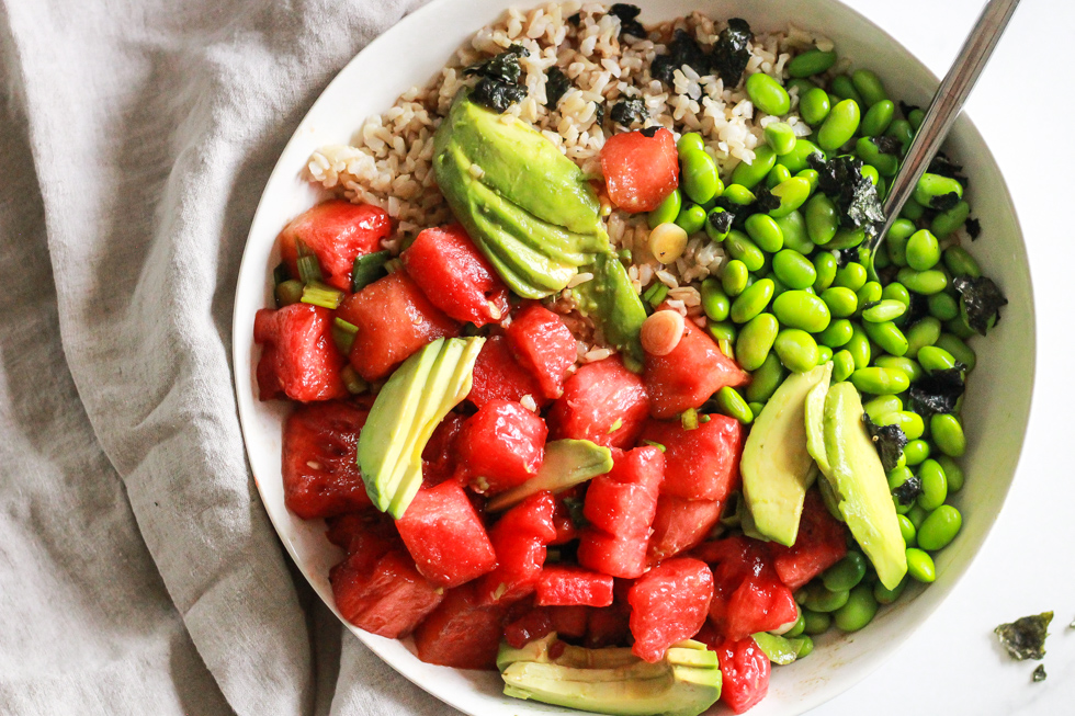 Horizontal image of watermelon poke bowls in a white bowl with linen napkin.