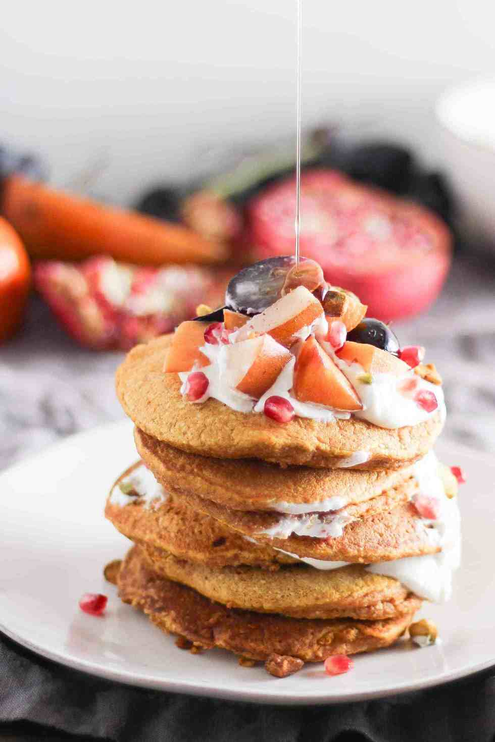 Tall stack of pumpkin pancakes with fruit and yogurt