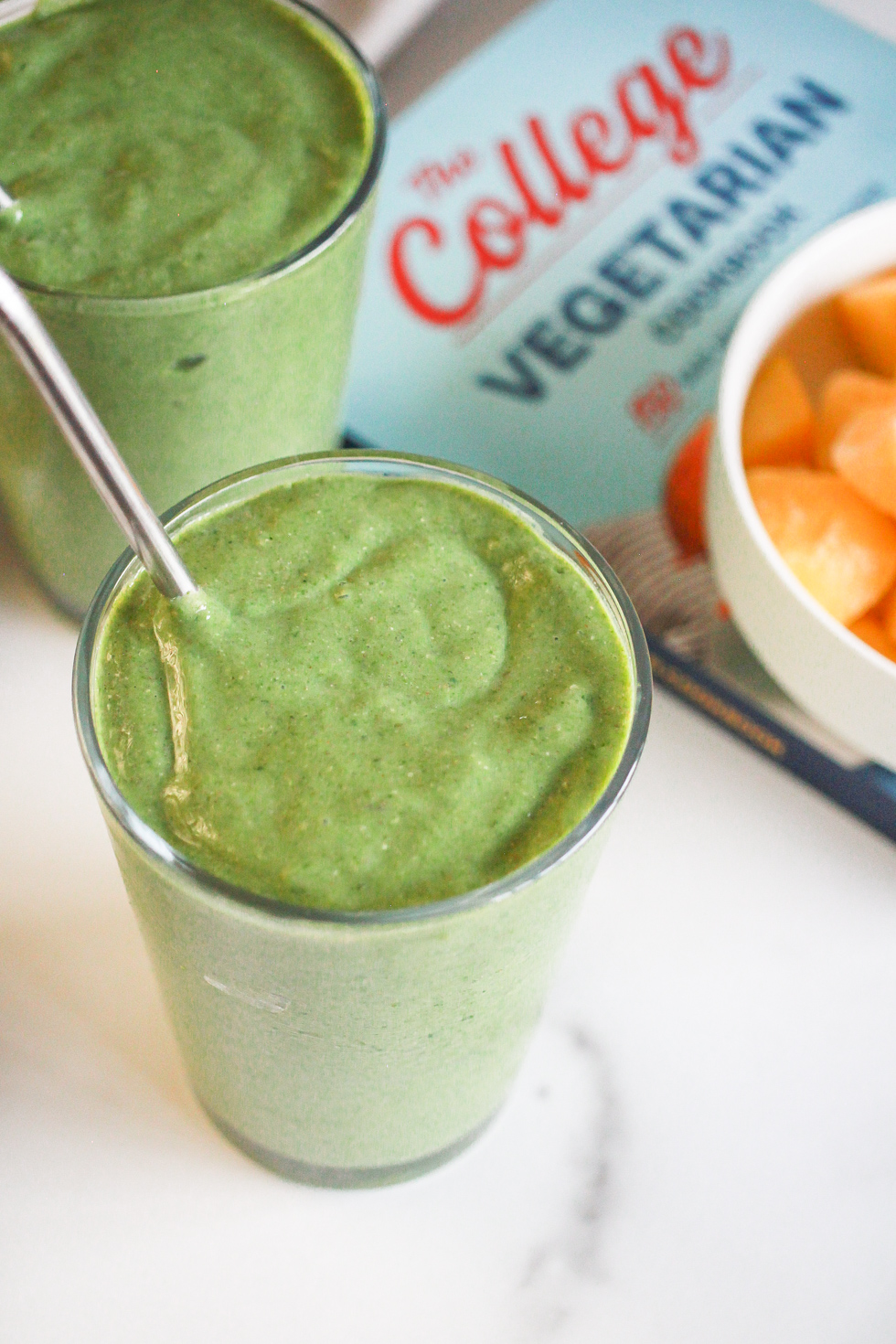 Two matcha smoothies in glasses next to a copy of The College Vegetarian Cookbook.