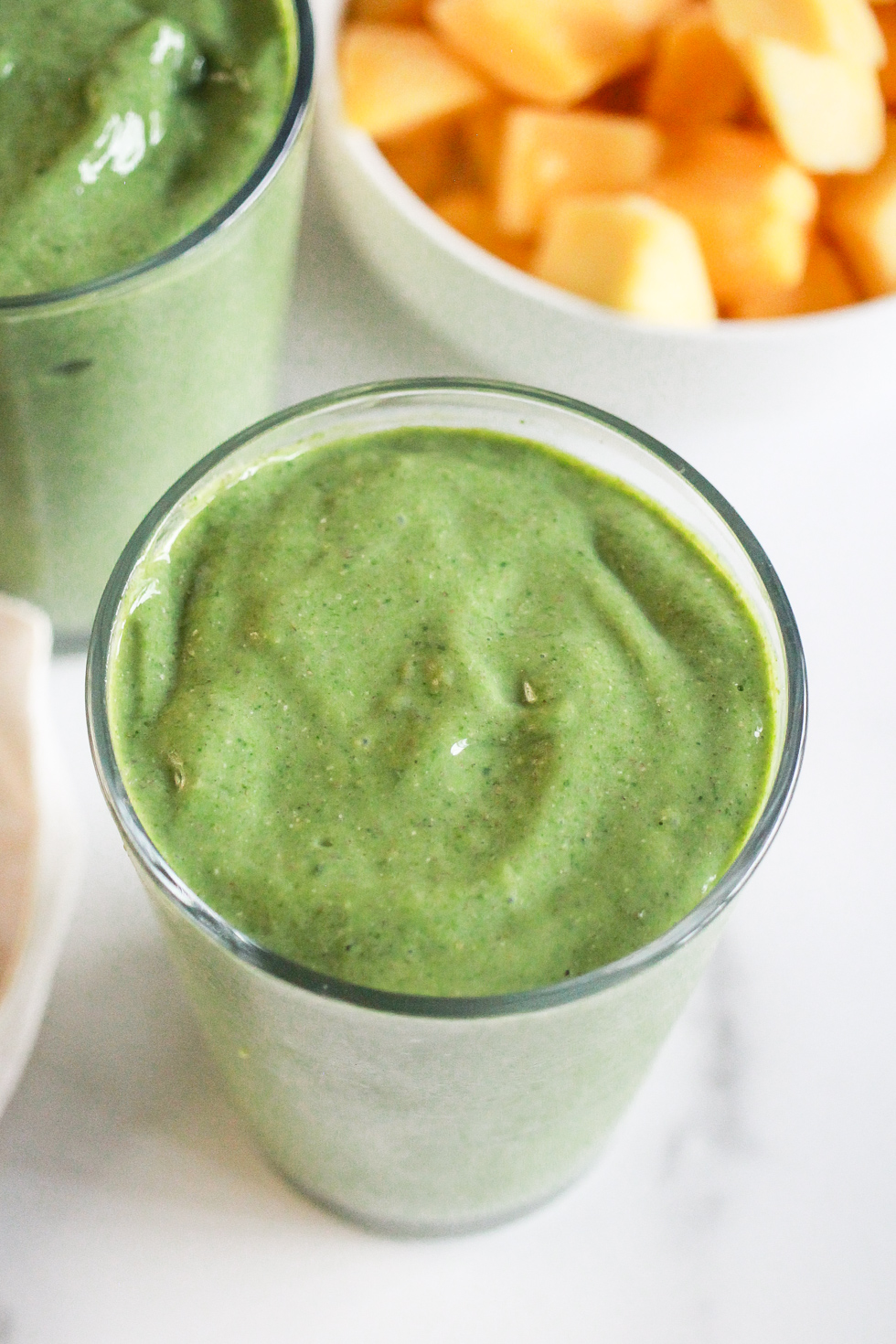 Matcha smoothie in front of a bowl of frozen mango chunks.