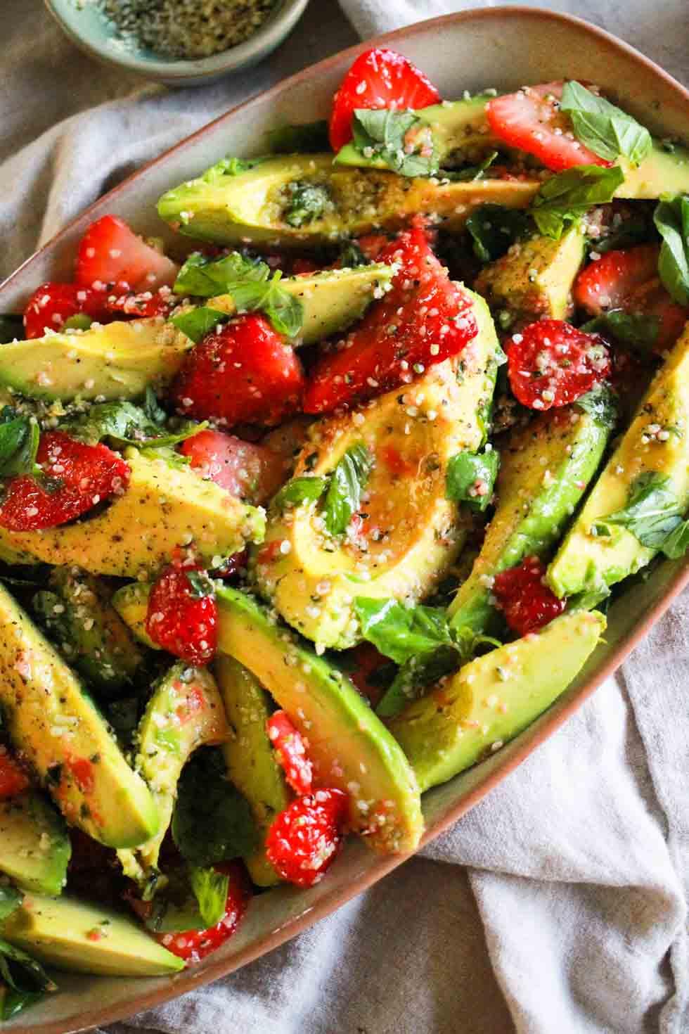 Strawberry avocado hemp salad on a rectangular platter with linen napkin.