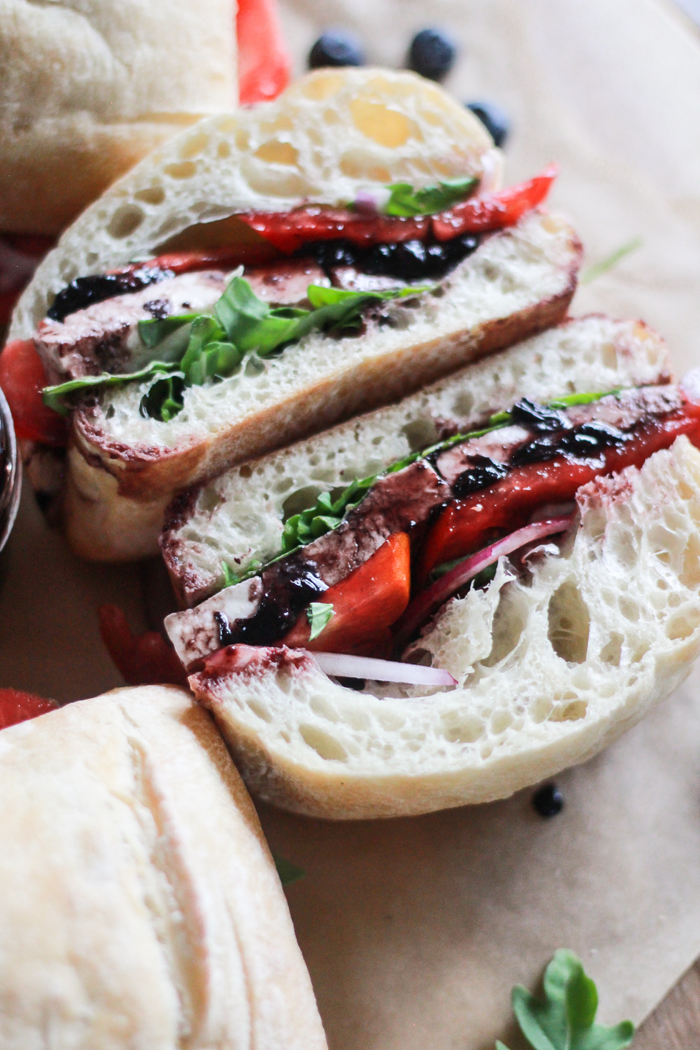 Halved Tomato Mozzarella Sandwich with arugula and blueberry balsamic sauce.