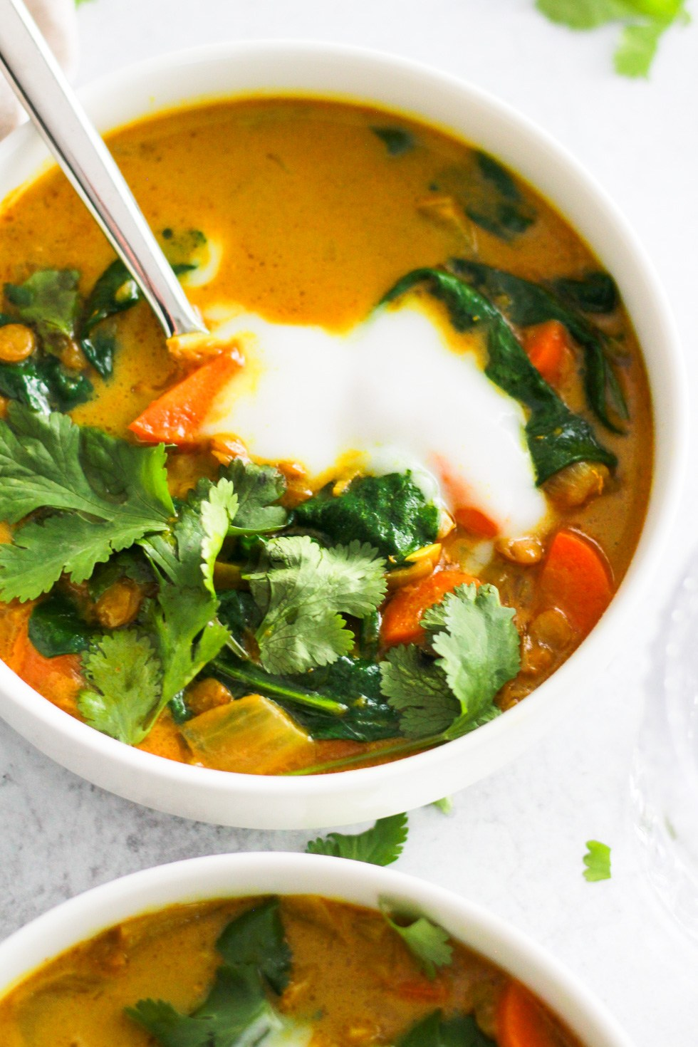 vegan soups like this yellow turmeric soup in a white bowl are easy college meals