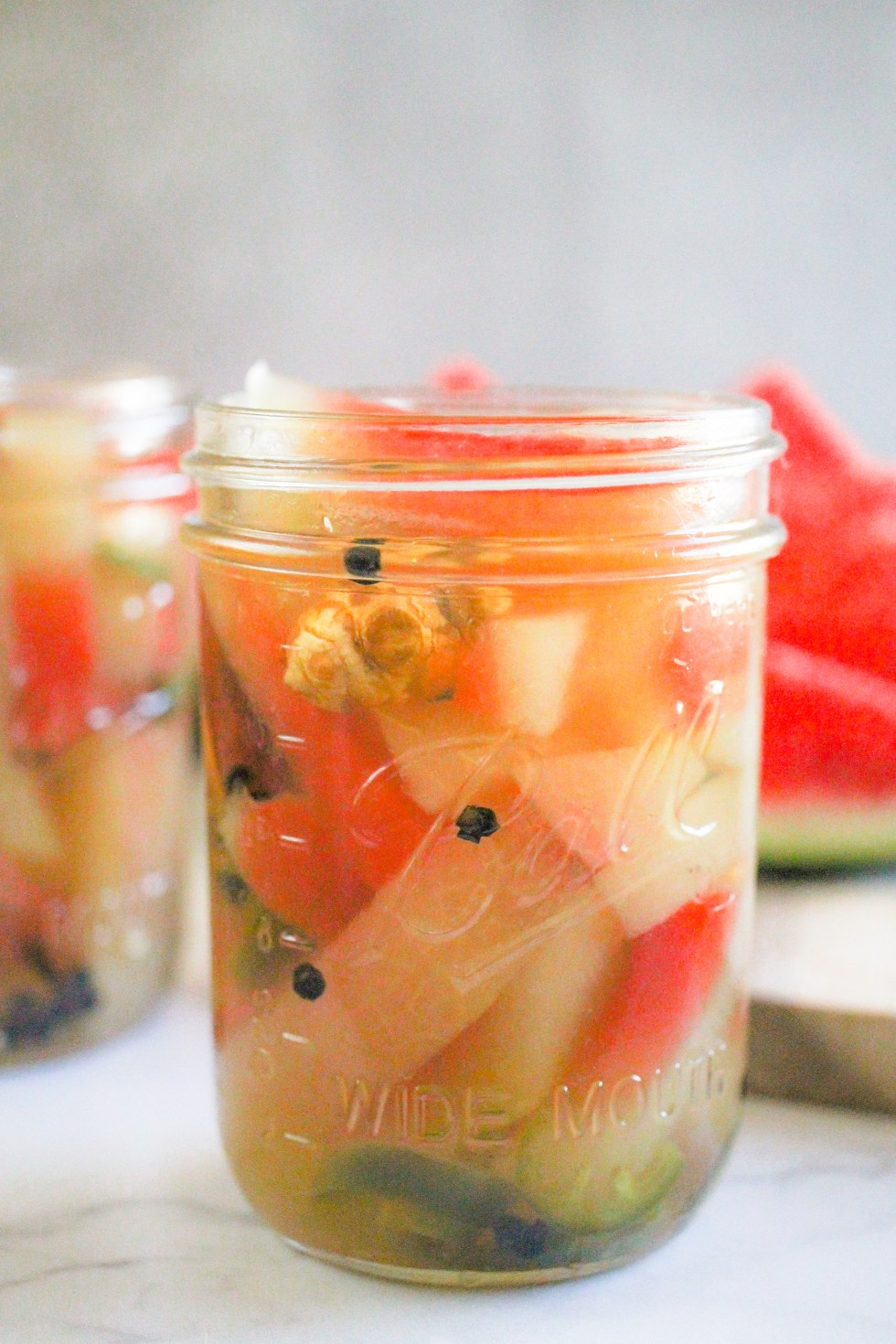 Straight shot of watermelon rind pickles in glass mason jars with gray background.
