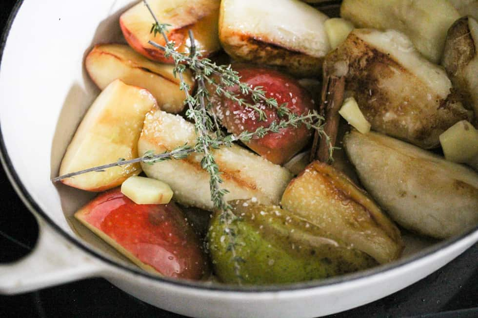 Apples, pears, cinnamon, and fresh thyme in a white Dutch oven.