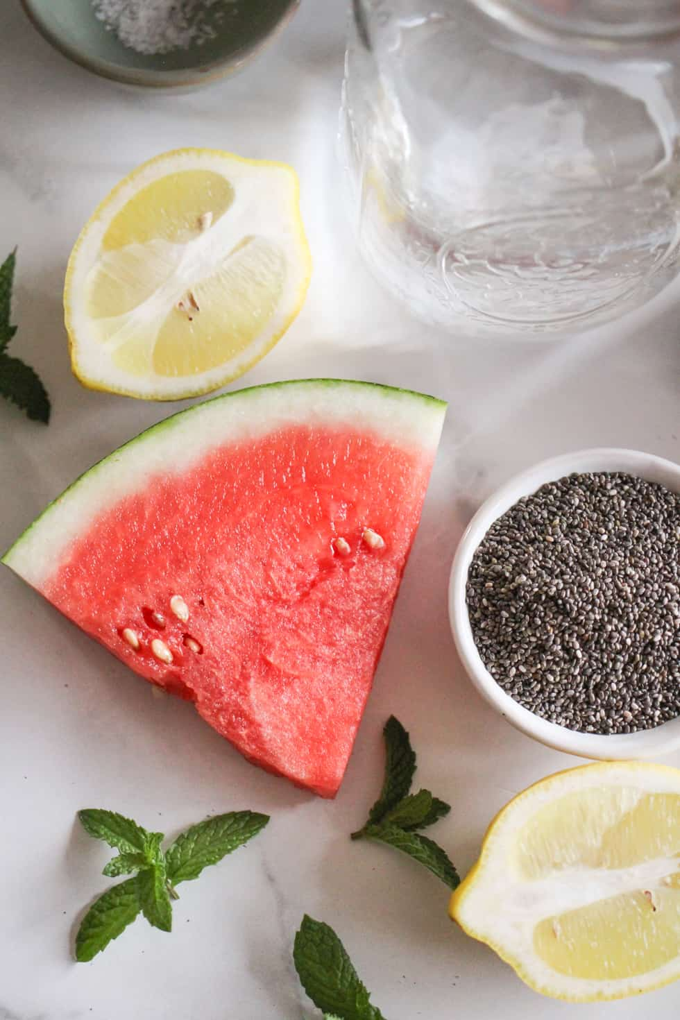 Sliced watermelon, lemon, chia seeds, fresh mint, and a jar of water.