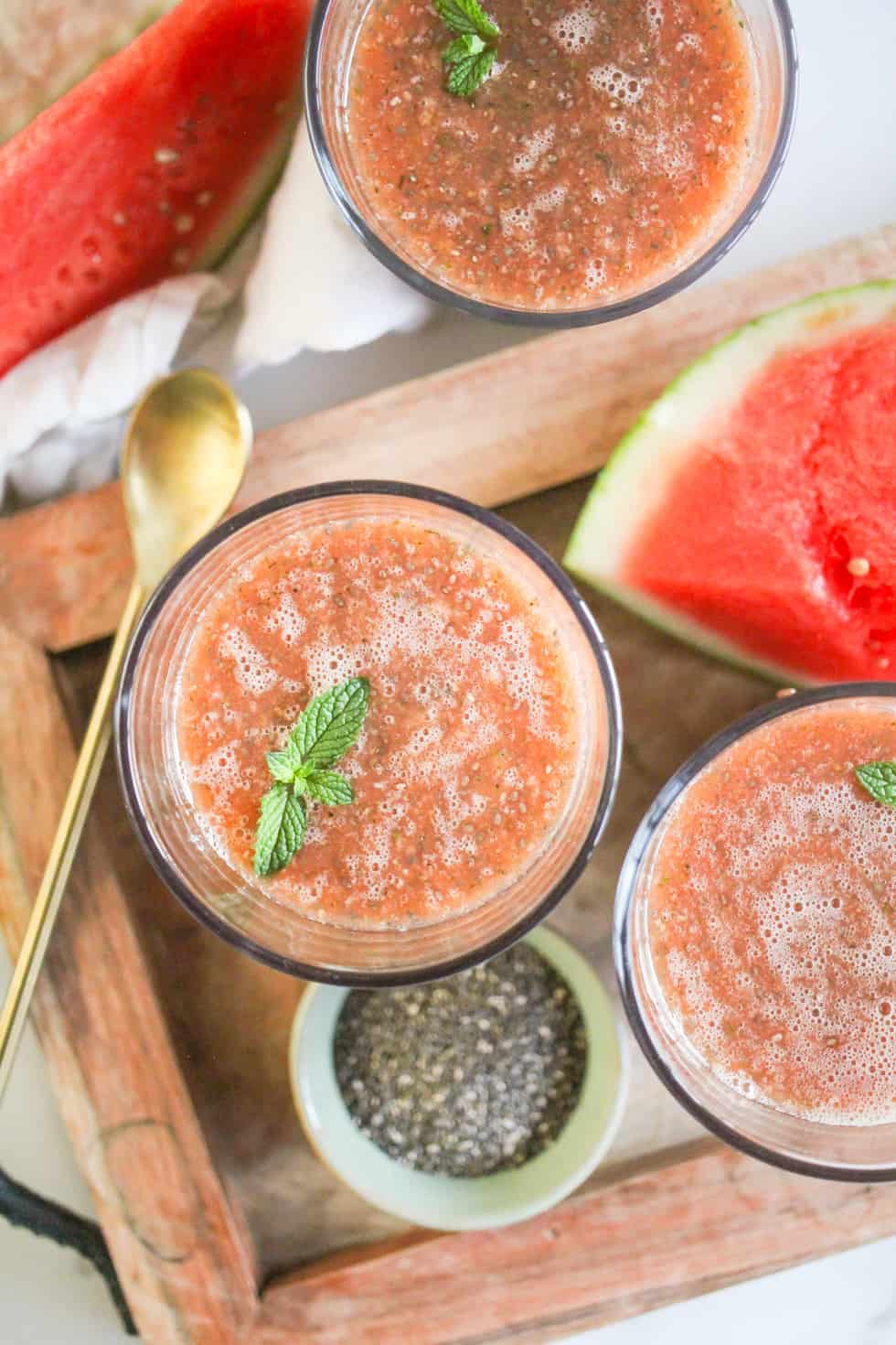Overhead image of Watermelon Chia Fresca in glasses on a wood tray with a gold spoon.