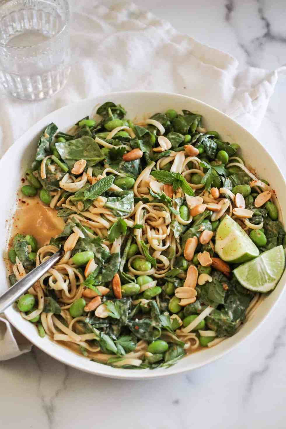 Peanut noodles with edamame and lime in a white bowl on a marble counter.