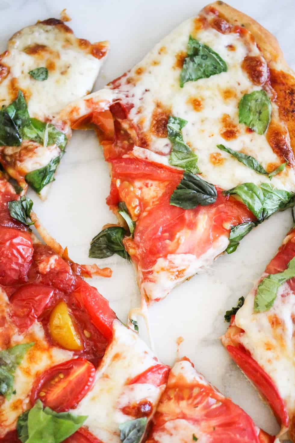 Closeup image of sliced Caprese Pizza on marble background.