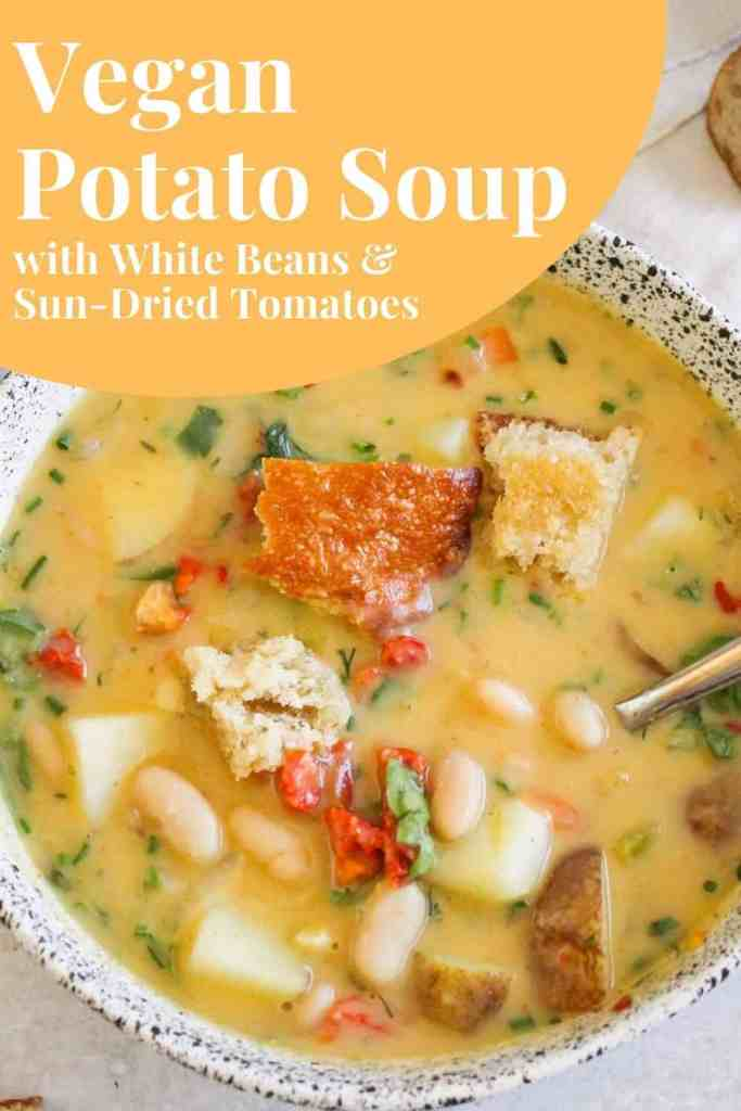 "Potato and bean soup in white bowl with yellow and white text that reads, ""Vegan Potato Soup with White Beans and Sun-Dried Tomatoes."""