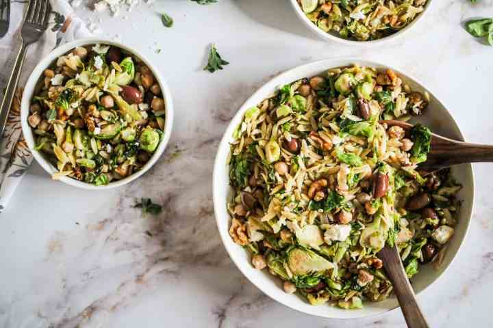 Horizontal image of brussels sprouts lemon orzo salad in white bowls on marble counter.