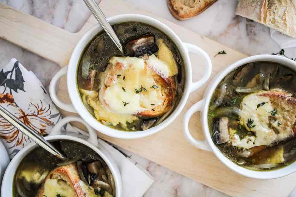 Horizontal image of white soup crocks with mushroom onion soup.