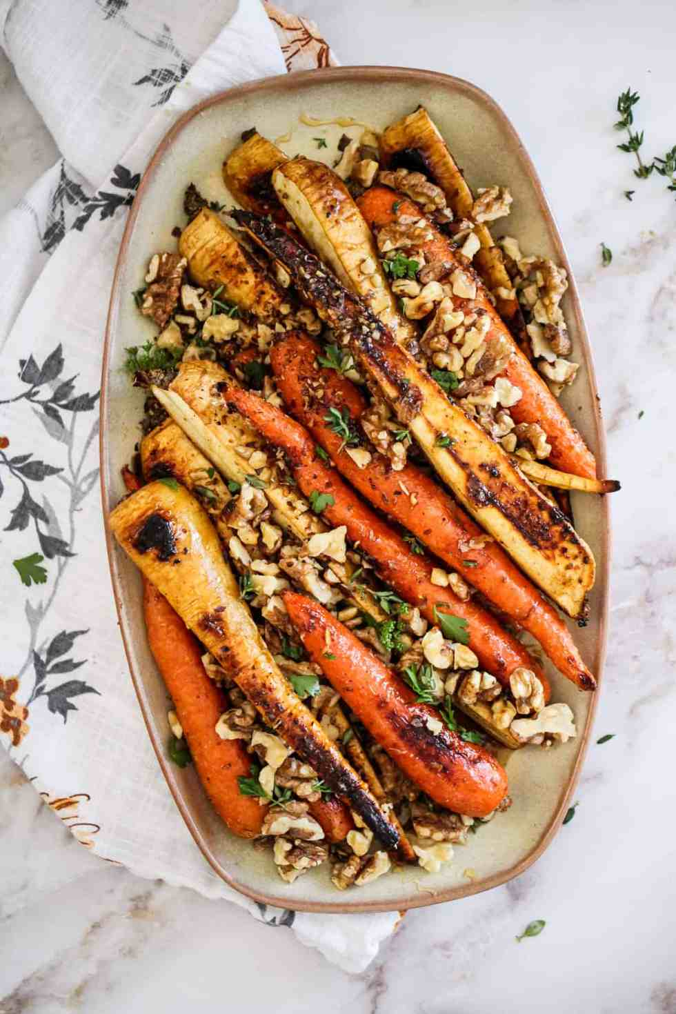 Platter of roasted vegetables topped with walnuts and herbs.