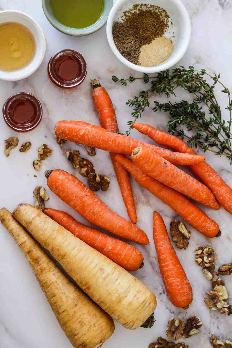 Parsnips, carrots, honey, walnuts, fresh thyme, and dry spices on white marble.