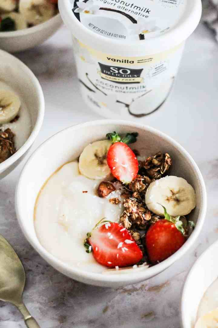 Closeup image of a vegan granola bowl with a container of So Delicious Yogurt Alternative behind it.