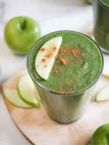 Green apple lentil smoothie in a glass and garnished with apple slices.