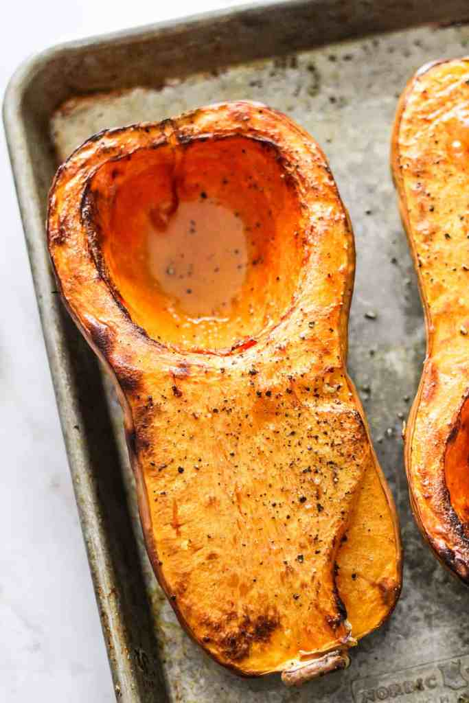 Closeup of a roasted butternut squash on a rimmed baking sheet.