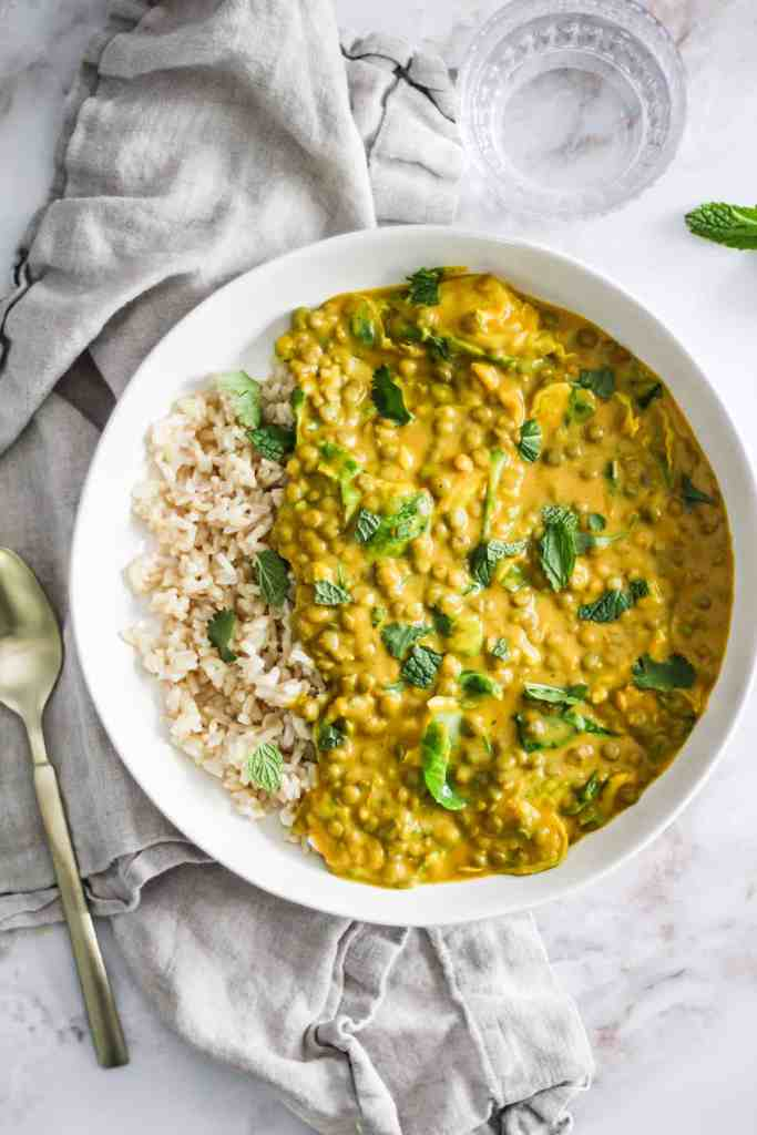 Yellow lentil curry in a white bowl with rice and fresh herbs.
