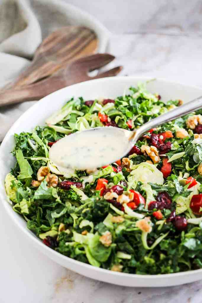 Using a spoon to drizzle white tahini dressing on top of a vegan green salad in a white bowl.