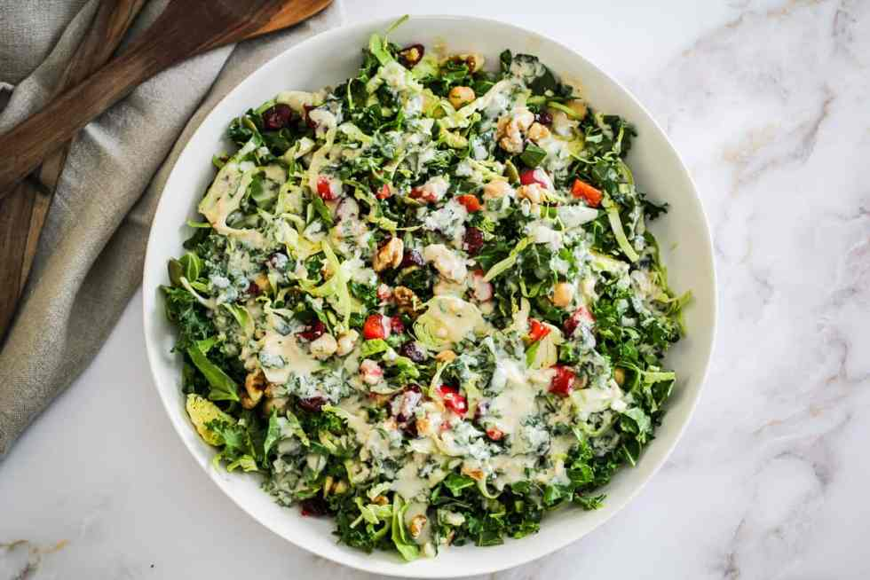 Horizontal image of a meal prep salad in a white bowl drizzled with creamy tahini dressing.