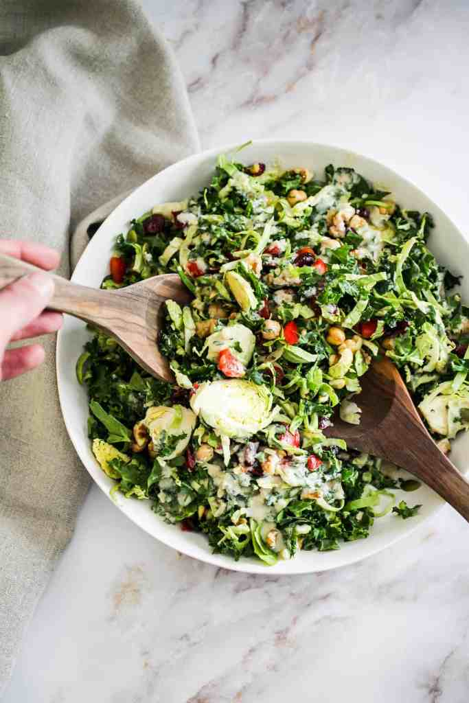 Tossing a Brussels sprouts and kale salad with wooden spoons.